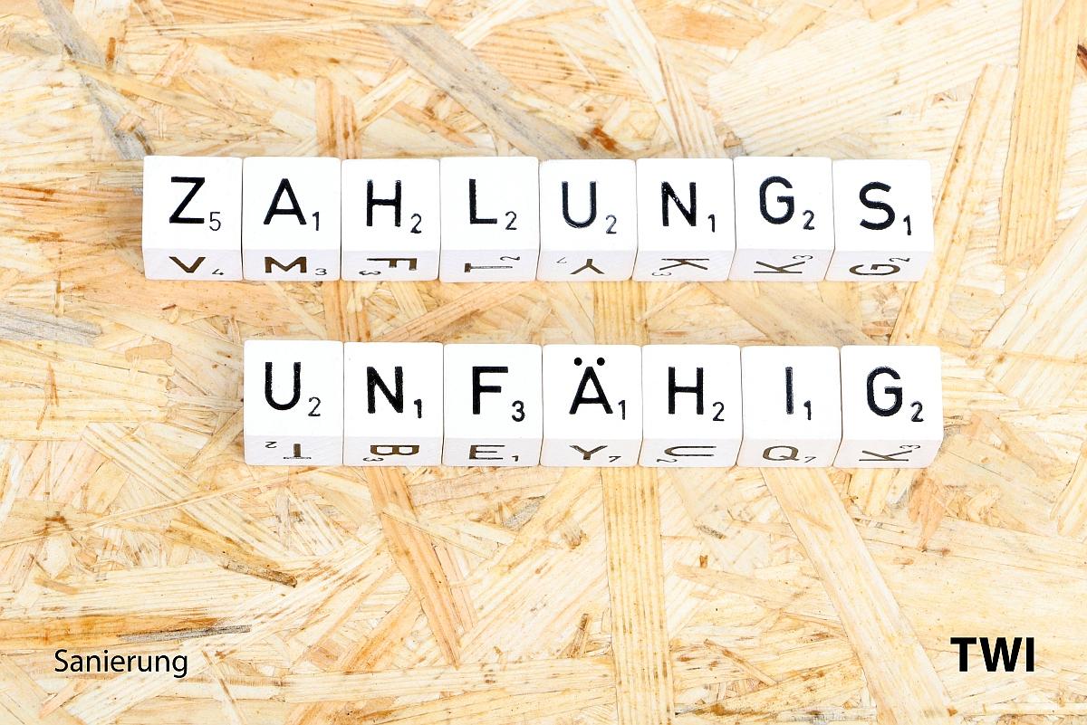 Das Wort zahlungsunfähig mit Buchstabenwürfeln geschrieben. Darunter die Worte: Sanierung - TWI.