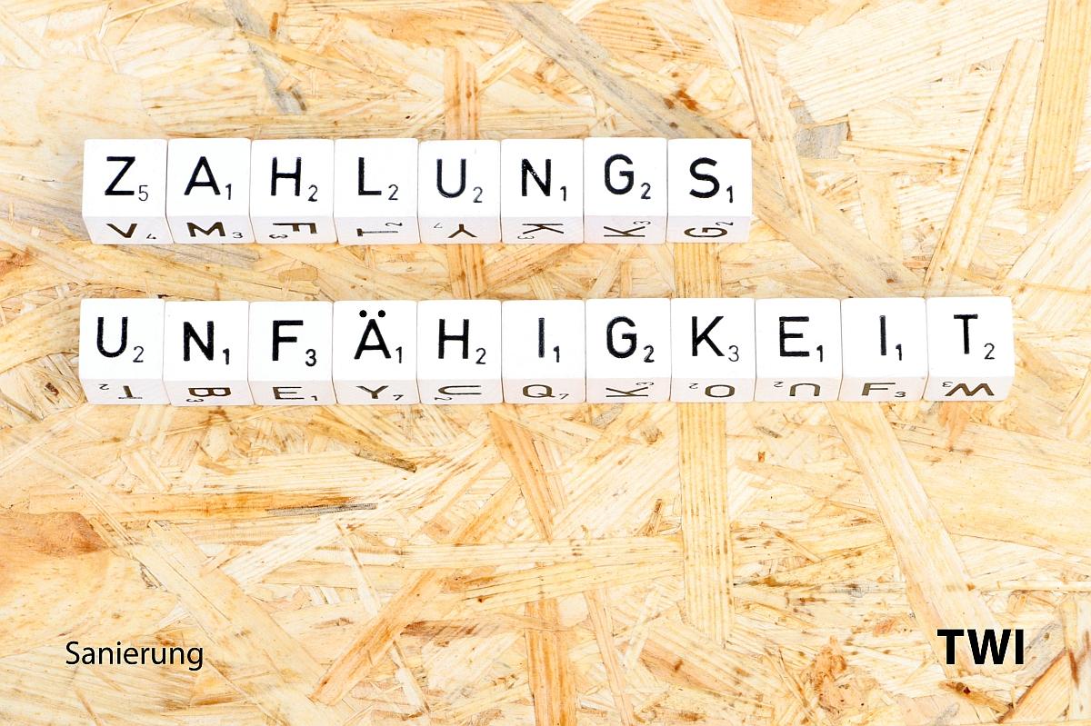 Das Wort Zahlungsunfähigkeit mit Buchstabenwürfeln geschrieben. Darunter die Worte: Sanierung, TWI