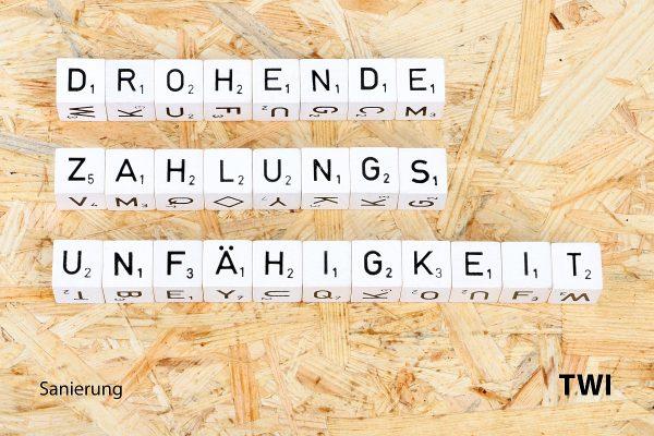 Die Worter Drohende Zahlungsunfähigkeit mit Buchstabenwürfeln geschrieben. Darunter die Worte: Sanierung, TWI.