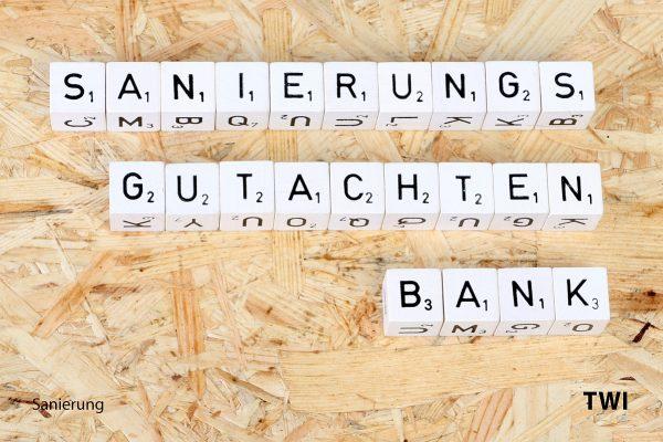 Text. Sanierungsgutachten Bank aus Buchstabenwürfeln geschrieben. Darunter Sanierung - TWI