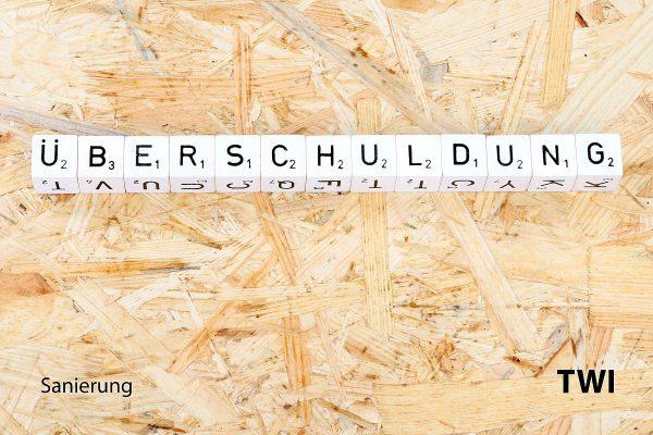 Das Wort Überschuldung mit Buchstabenwürfeln geschrieben. Darunter die Worte: Sanierung, TWI.